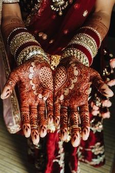 Traditionelle indische herzverzierung auf den händen gefärbt durch hennastrauch und brautarmbänder in den bordeauxfarben