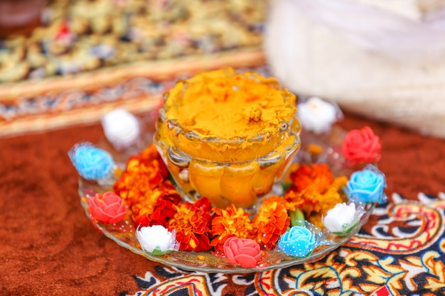 Traditionelle indische hochzeit: kurkumapulver in der schüssel für die haldi-zeremonie