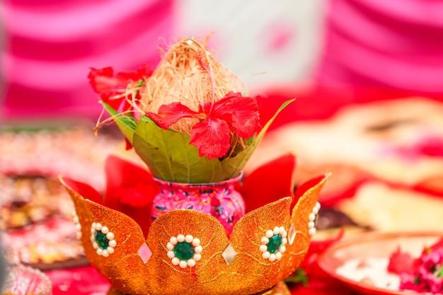 Traditionelle indische hochzeitszeremonie: kokosnuss in dekorativem coper kalash Premium Fotos