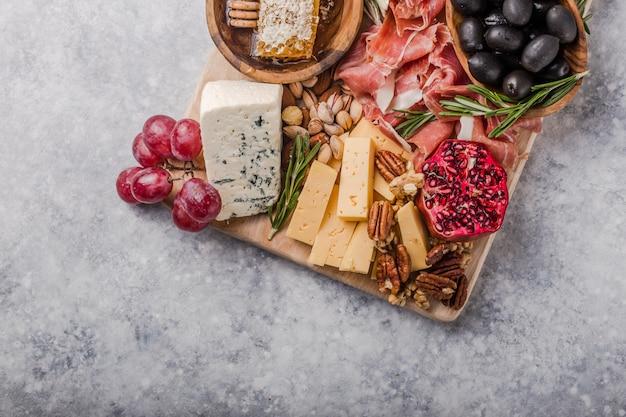 Traditionelle italienische antipasti-platte. verschiedene käsesorten auf holzschneidebrett. brie-käse, cheddar-scheiben, gogonzola, walnuss-trauben, oliven, schinken, rosmarin und ein glas rotwein. draufsicht