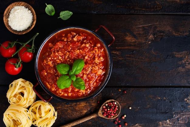 Traditionelle italienische bolognese-sauce im topf eine alte dunkle holzoberfläche. ansicht von oben, textfreiraum