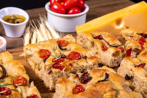 Traditionelle italienische focaccia mit kirschtomaten, schwarzen oliven und rosmarin.