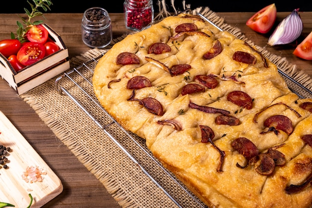 Traditionelle italienische focaccia mit peperoni, kirschtomaten, schwarzen oliven, rosmarin und zwiebeln - hausgemachte fladenbrot-focaccia.