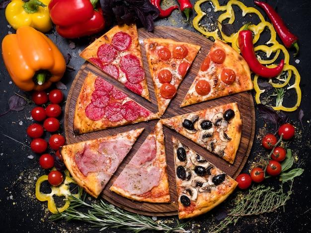 Traditionelle italienische küche. leckeres pizzastück quattro stagioni mit schinken prosciutto tomaten oliven und champignons