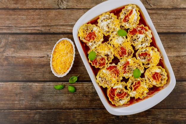 Traditionelle italienische lasagne mit käse und basilikum auf hölzernem hintergrund