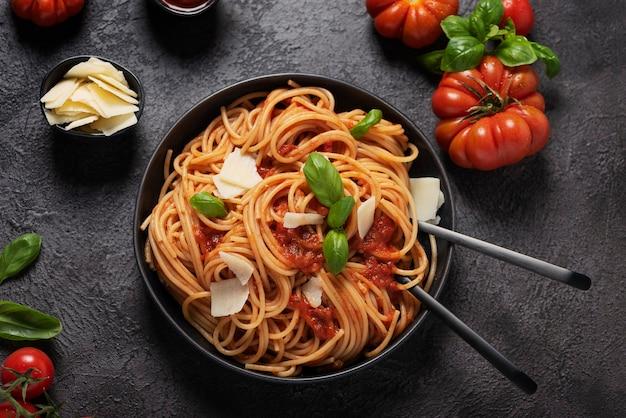 Traditionelle italienische nudeln mit tomatensauce, basilikum und käse auf dem schwarzen hintergrund, ansicht von oben nach unten mit kopienraum