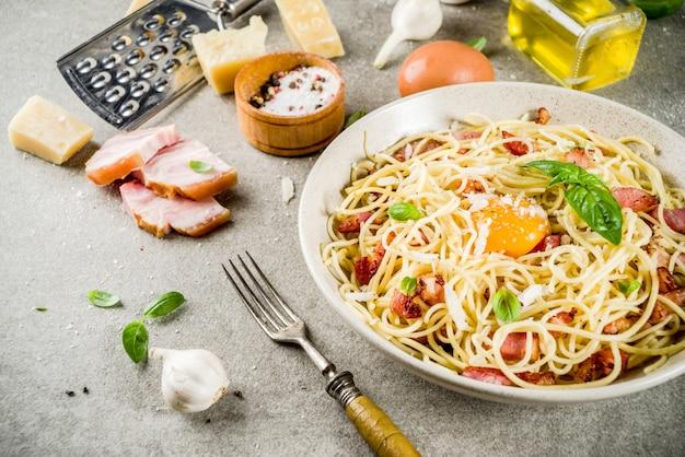 Traditionelle italienische pasta, spaghetti carbonara mit speck, sahnesauce, parmesankäseparmesan, eigelb und frischem basilikum