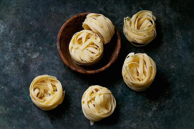 Traditionelle italienische pasta tagliatelle in einer holzschale. draufsicht. flache lage.