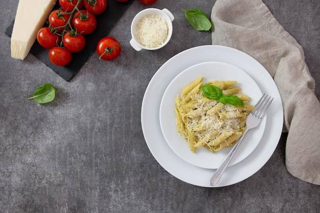 Traditionelle italienische penne-nudeln mit pesto, basilikum, tomaten und parmesan.