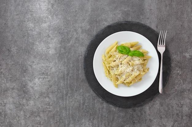 Traditionelle italienische penne-nudeln mit pesto, basilikum und parmesan auf einem dunklen schieferteller.