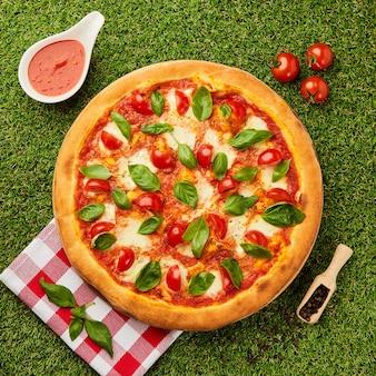 Traditionelle italienische pizza margarita mit käse, tomate und basilikum auf grünem gras