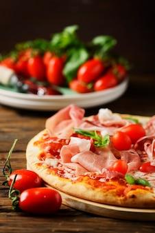 Traditionelle italienische pizza mit mozzarella, tomate und speck, selektivem fokus und copyspace