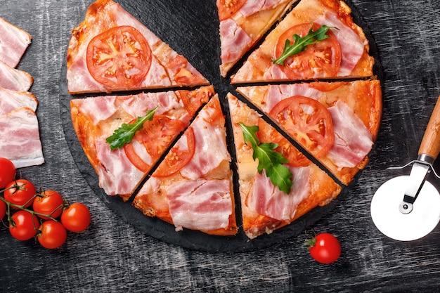 Traditionelle italienische pizza mit mozzarellakäse, schinken, tomaten, pfeffer, pepperoni-gewürzen und frischem rucola