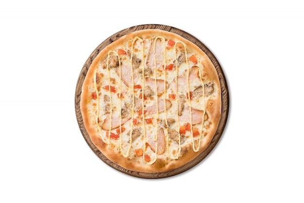 Traditionelle italienische pizza mit speck, tomaten und käsesoße auf dem hölzernen brett lokalisiert
