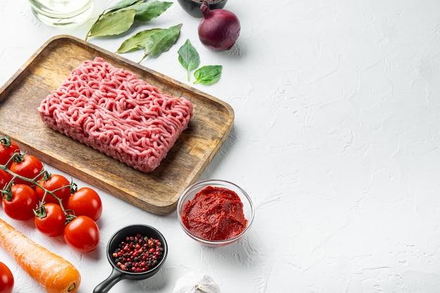 Traditionelle italienische tomatensauce bolognese mit zutaten, hackfleisch-tomaten und kräutern, auf holztablett, auf weißem stein