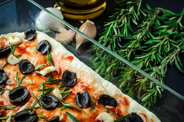 Traditionelle italienische vegetarische focaccia aus hausgemachtem brot mit oliven, rosmarin und knoblauch