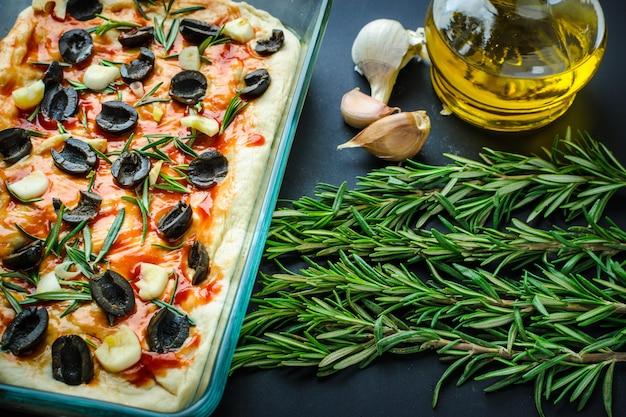 Traditionelle italienische vegetarische focaccia aus hausgemachtem brot mit oliven, rosmarin