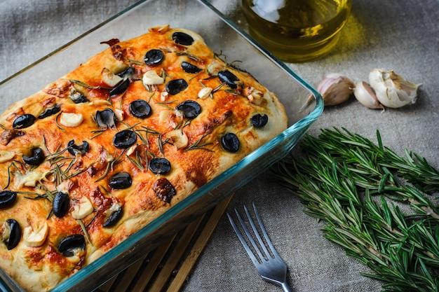 Traditionelle italienische vegetarische focaccia aus selbstgebackenem brot mit oliven, rosmarin und knoblauch