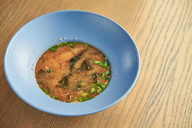 Traditionelle japanische misosuppe in einer blauen schüssel auf einer holzwand. gesunde ernährung. nahansicht