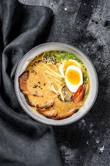 Traditionelle japanische suppenramen mit fleischbrühe, asiatischen nudeln, seetang, geschnittenem schweinefleisch, eiern. schwarzer hintergrund. draufsicht