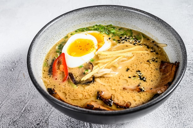 Traditionelle japanische suppenramen mit fleischbrühe, asiatischen nudeln, seetang, geschnittenem schweinefleisch, eiern. weißer hintergrund. draufsicht