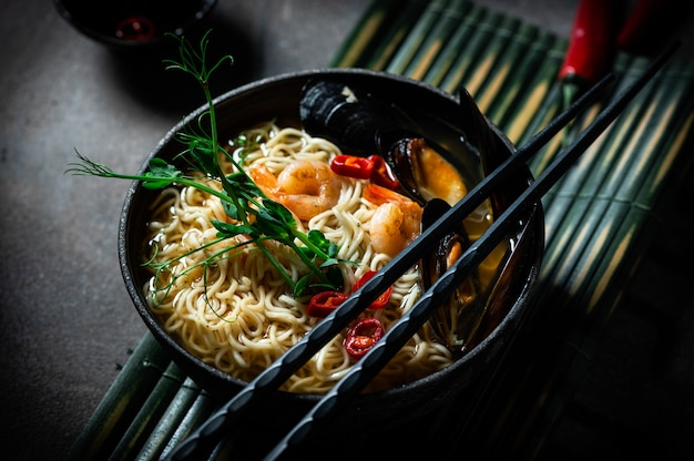 Traditionelle japanische suppenramen mit garnelen, asiatischen nudeln, muscheln chili-pfeffer auf dunklem hintergrund. essen im asiatischen stil. platz für text. nudeln mit meeresfrüchten und microgreen
