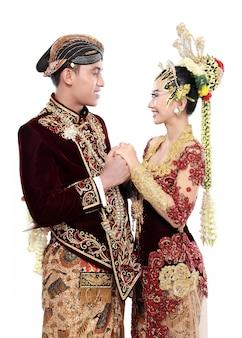 Traditionelle java-hochzeitspaar ehemann und ehefrau halten sich gegenseitig
