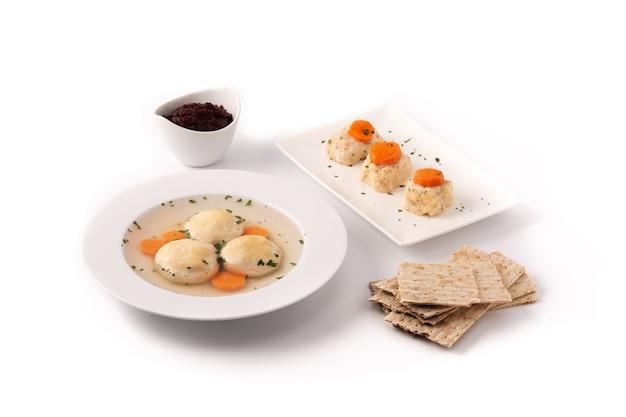 Traditionelle jüdische matzahballsuppe, gefilte fisch und matzenbrot isoliert auf weißem hintergrund