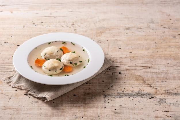 Traditionelle jüdische mazza-ball-suppe auf holztisch