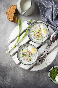 Traditionelle kalte russische suppe mit wurst, kartoffeln, gekochtem ei, frischem gemüse, frühlingszwiebeln und dill