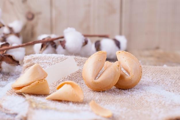 Traditionelle kekse mit wünschen für weihnachten und neujahr, auf einem holztisch und einem ast mit baumwolle
