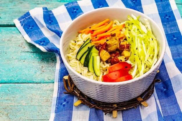 Traditionelle koreanische nudelschale mit geräuchertem hähnchen, frisch geschnittenem gemüse und sesam