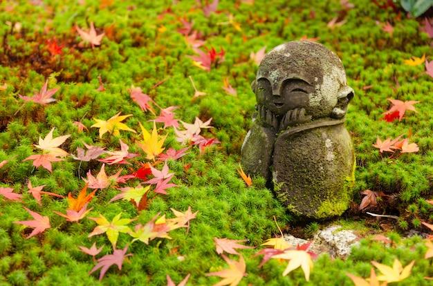 Traditionelle lächelnde kleine stein- oder jizo-buddha-mönchstatue mit bunten rotahornblättern auf grünem gras rieb im japanischen garten mit während des sonnenaufgangs, herbstsaison an enkoji-tempel in kyoto, japan