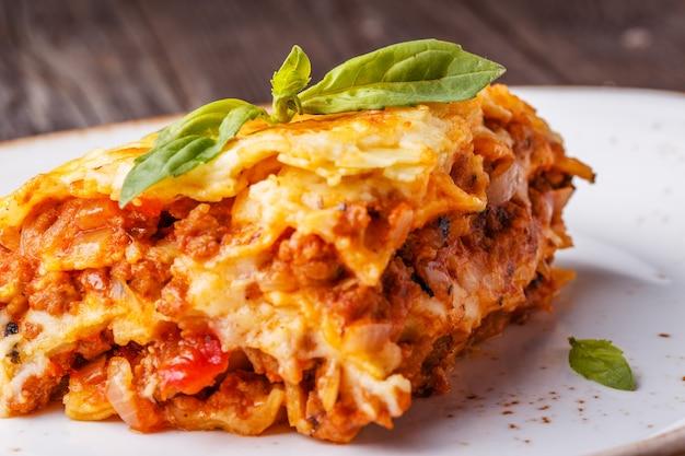 Traditionelle lasagne mit hackfleisch-bolognese-sauce und bechamelsauce mit basilikumblättern.