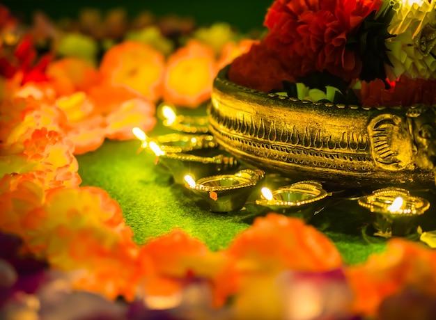 Traditionelle lehm-diya lampen beleuchteten mit blumen für diwali-festivalfeier.