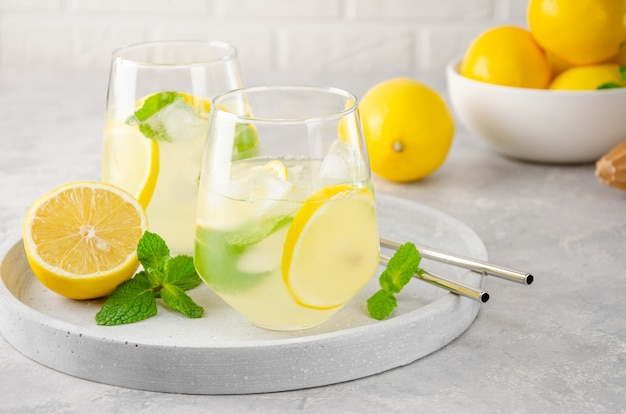 Traditionelle limonade mit zitrone, minze und eis in einem glas mit metallstroh auf einem grauen betonhintergrund.