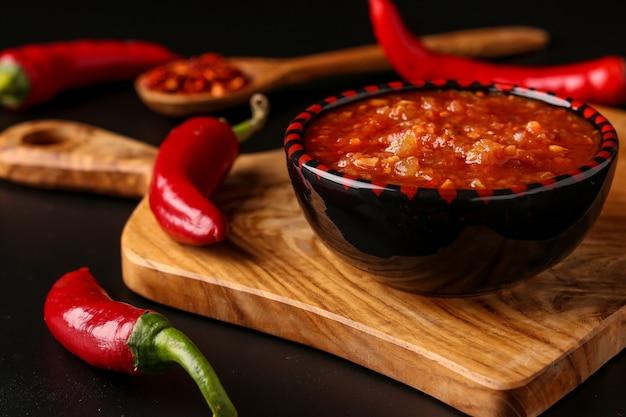 Traditionelle maghrebi hot chili pfeffersauce paste harissa auf dunklem hintergrund, tunesien und arabische küche, horizontale ausrichtung, nahaufnahme