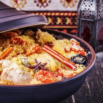 Traditionelle marokkanische hühnchen-tajine mit getrockneten früchten und gewürzen.