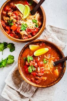 Traditionelle mexikanische bohnensuppe mit fleisch und käse in der hölzernen schüssel