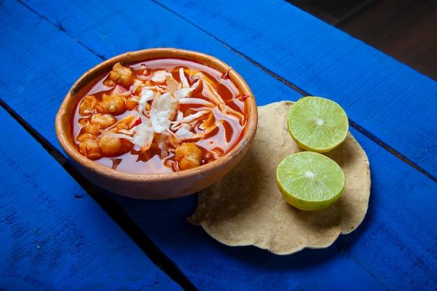 Traditionelle mexikanische rote pozole-suppe mit tostada und limetten auf blauem hintergrund