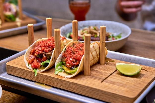 Traditionelle mexikanische schweinefleisch-tacos mit rindfleisch, tomaten, avocado, chili und zwiebeln in gelber maistortilla namens al pastor