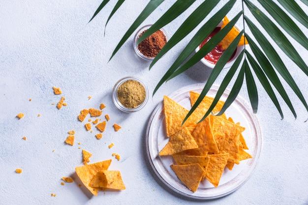 Traditionelle mexikanische snacknachos mit soße, gewürzen und palmzweig auf weißem hintergrund