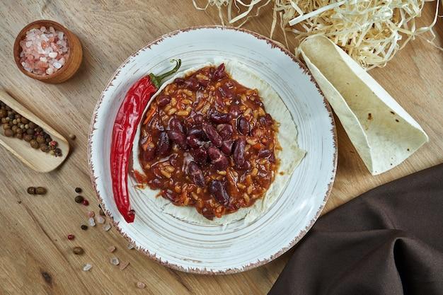Traditionelle mexikanische tacos mit bohnen, chilischoten in weißer keramikplatte auf holztisch. leckere chili con carne burritos in maistacos