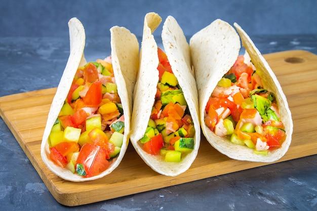 Traditionelle mexikanische tacos mit fleisch und gemüse auf hölzernem hintergrund