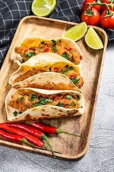 Traditionelle mexikanische tacos mit petersilie, käse und chilischoten. weißer hintergrund.