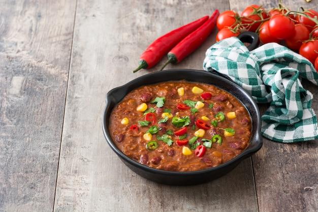 Traditionelle mexikanische tex mex chili con carne in einer bratpfanne auf hölzernem tischkopierraum
