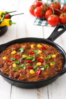 Traditionelle mexikanische tex mex chili con carne in einer pfanne auf weißem holztisch