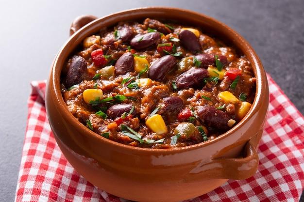 Traditionelle mexikanische tex-mex-chili con carne in einer schüssel auf schwarzem hintergrund.