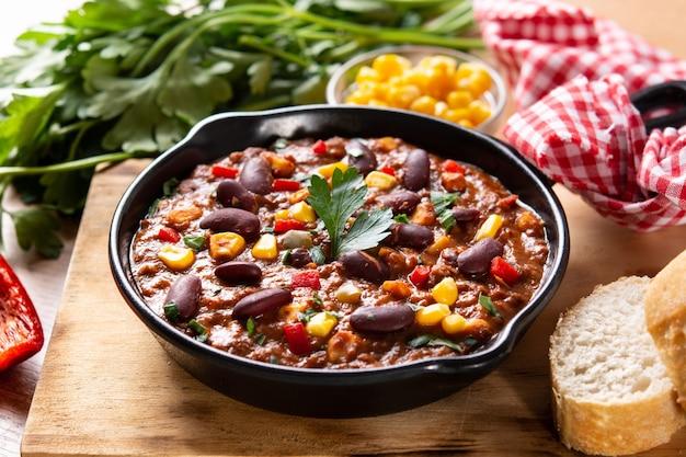 Traditionelle mexikanische tex mex chili con carne in eisenpfanne auf holztisch