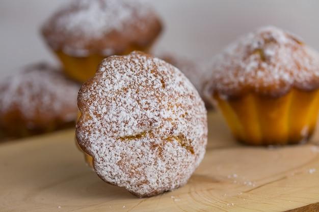 Traditionelle muffins oder gebackene grundlegende kleine kuchen schließen oben, selektiver fokus